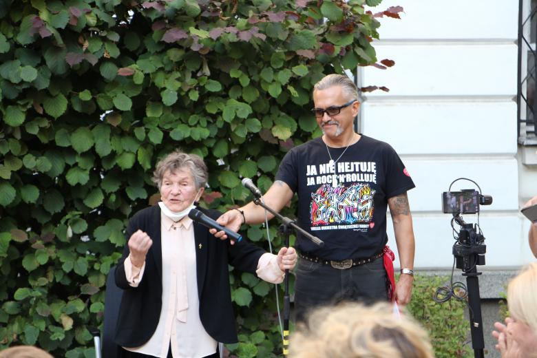 Starsza kobieta przemawia do ludzi żywo gestykulując