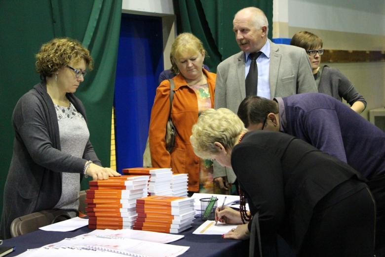 zdjęcie: kilka osób stoi przy stoliku na którym leżą publikacje