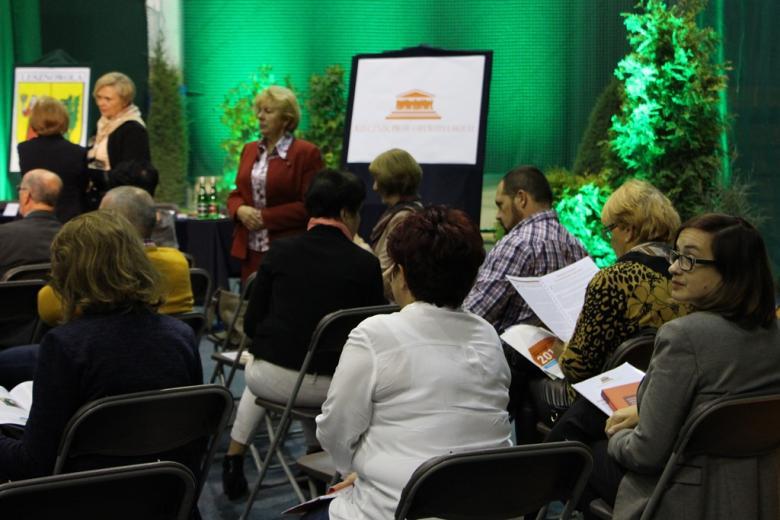 zdjęcie: kilkaście osób siedzi na krzesłach oglądają broszury informacyjne