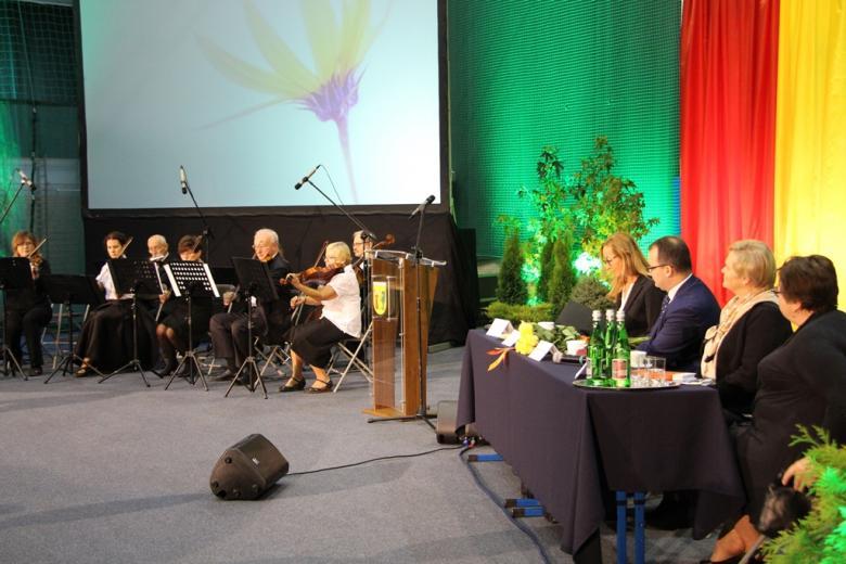 zdjęcie: po lewej stronie widać członków orkiestry, po prawej siedzą cztery osoby za stołem prezydialnym