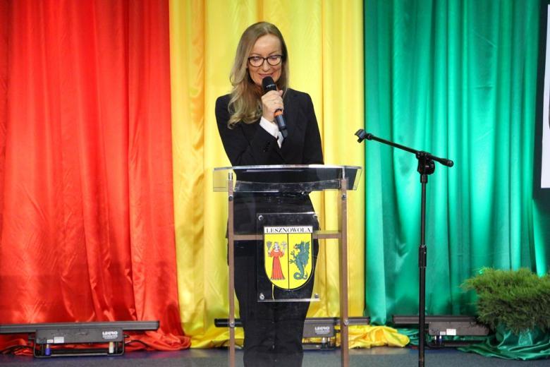 zdjęcie: kobieta w długich blond włosach, w ciemnym garniturze mówi do mikrofonu przy mównicy