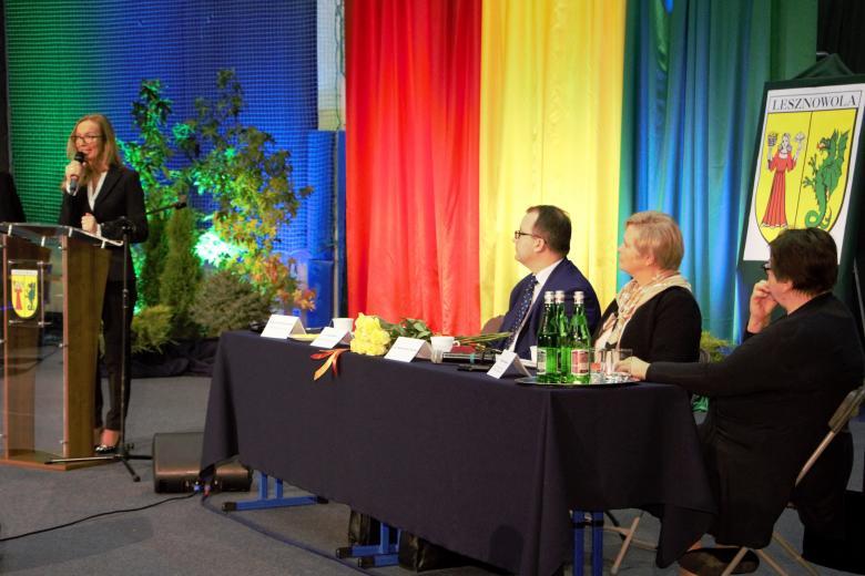 zdjęcie: po prawej stronie siedzą czterey osoby przy stole prezydialnym, po lewej przy mównicy stoi kobieta