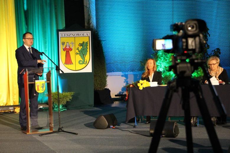 zdjęcie: mężczyzna w garniturze stoi przy mównicy, przed nim stoi kamera