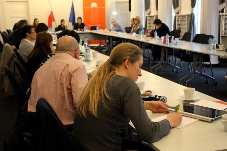 zdjęcie: przy stołach ustawionych naprzeciw siebie siedzi kilkanaście osób