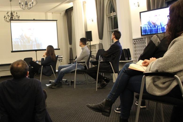 zdjęcie: kilka osób siedzi na sali i ogląda film wyświetlany przez projektor