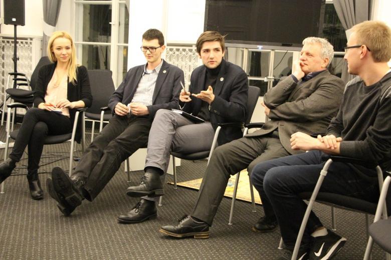 zdjęcie: kilka osób siedzi na krzesłach, jeden z mężczyzn gestykuluje