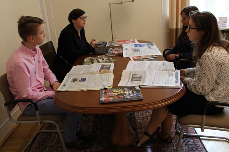 zdjęcie: przy stle, na którym leżą gazety siedzą cztery osoby