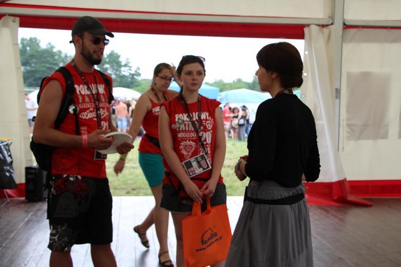 zdjęcie: kilka osób w czerwonych koszukach stoi w namiocie i rozmawia z kobietą