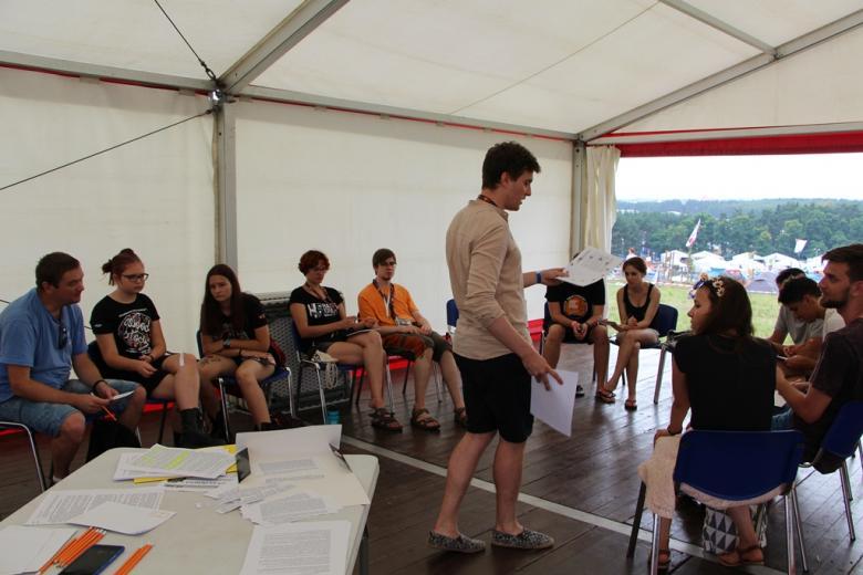 zdjęcie: w namiocie na krzesłach siedzi kilkanaście osób