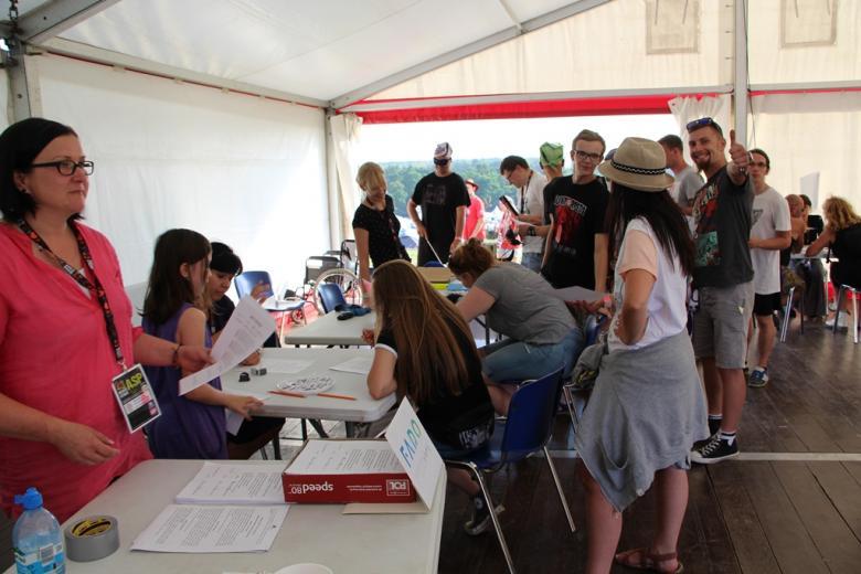 zdjęcie: kilkanaście osób stoi w kolejce przy stolikach