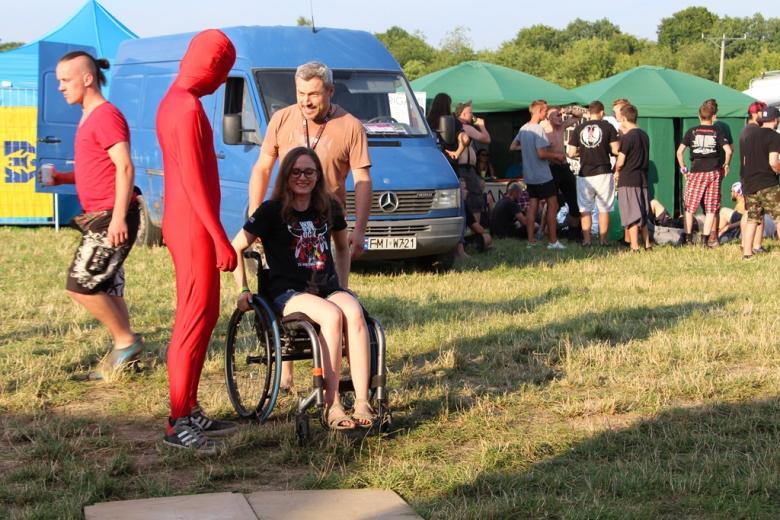 zdjęcie: na wózku siedzi młoda dziewczyna za nią stoi mężczyzna, obok nich człowiek w czerwonym kombinezonie