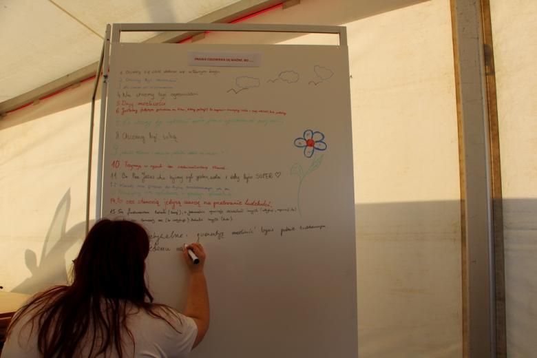 zdjęcie: przy białej tablicy stoi dziewczyna, która na niej pisze