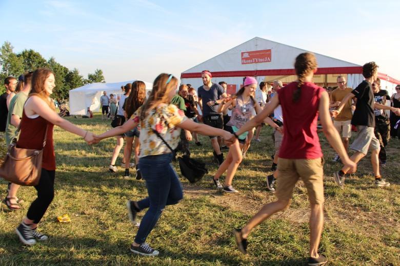 zdjęcie: kilkanaście osób tańczy w kręgu trzymając się za ręce