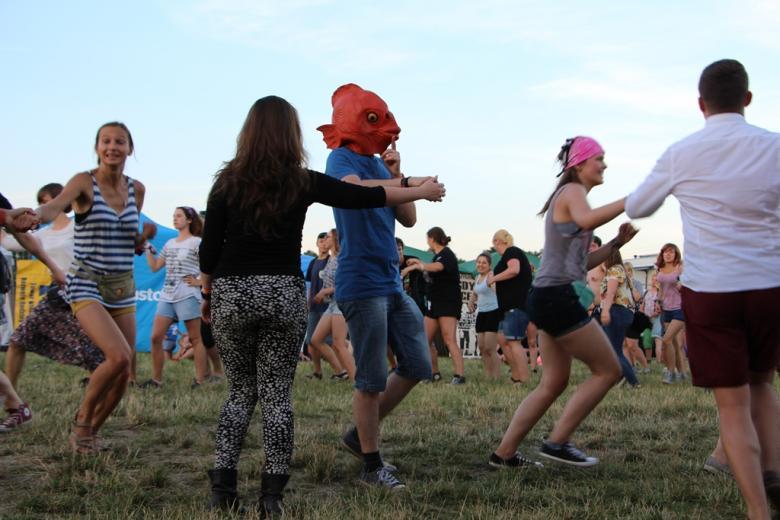 zdjęcie: kilka osób tańczy na trawie, mężczyzna po środku ma założoną maskę ryby