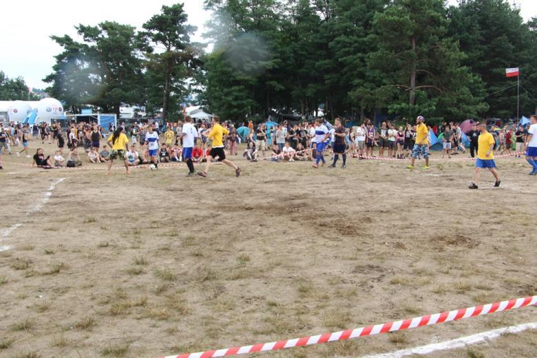 zdjęcie: kilkanaście osób gra na wyznaczonym na ziemi boisku