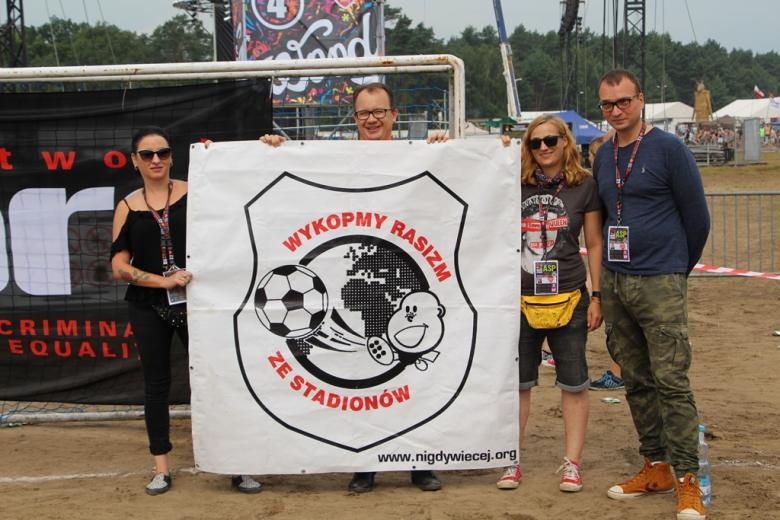 zdjęcie: cztery osoby stoją trzymając ogromny baner z napisem: Wykopmy rasizm ze stadionów