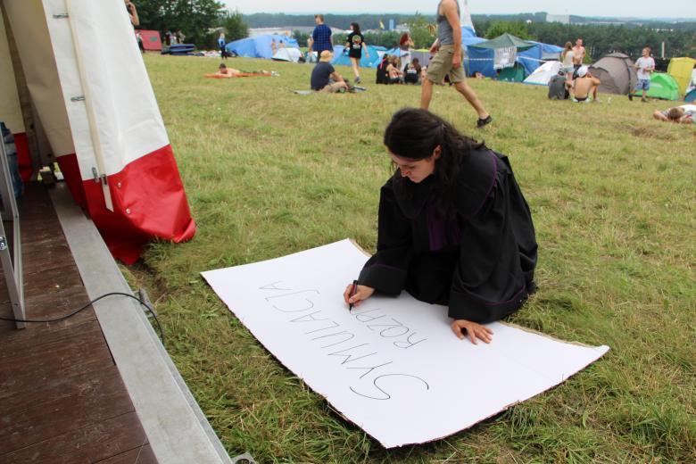 zdjęcie: kobieta w czarnej todze kłeczy na trawie i rysuje plakat