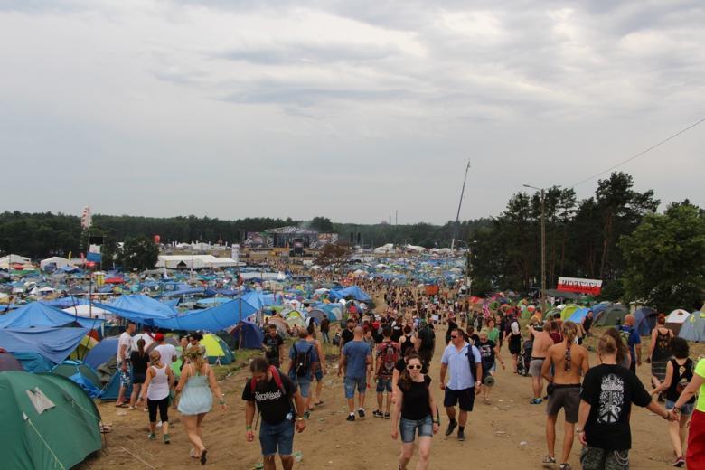 zdjęcie: na pierwszy planie pole namiotowe i idący ludzie, w tle ogromna scena