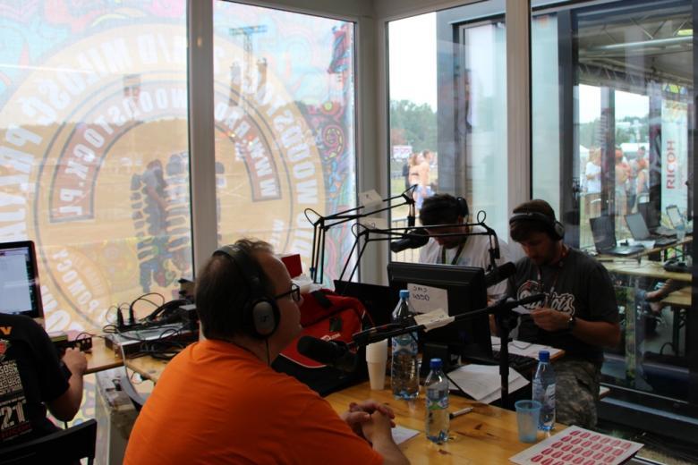 zdjęcie: mężczyzna w pomarańczowej koszulce siedzi przy mikrofonie