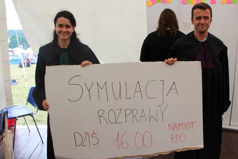 zdjęcie: kobieta i mężczyzna stoją w togach i trzymają karton z napisem: symulacja rozprawy na namiocie RPO o godz. 16