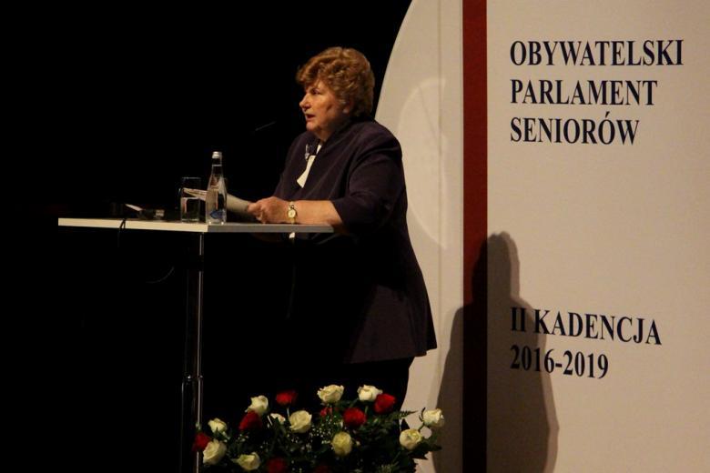 zdjęcie: kobieta w ciemnym żakiecie stoi przy mównicy