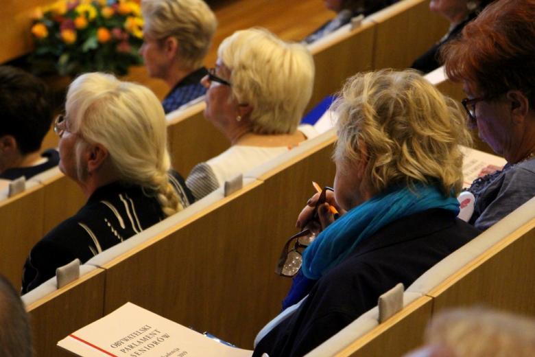 zdjęcie: kilka osób siedzi i przysłuchuje się wystąpieniom