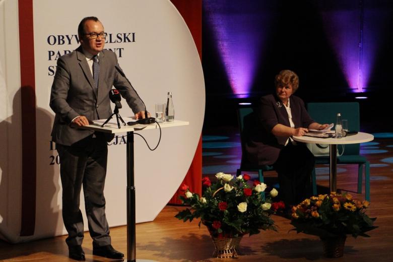 zdjęcie: mężczyzna w jasnym garniturze stoi przy mównicy, za nim siedzi kobieta