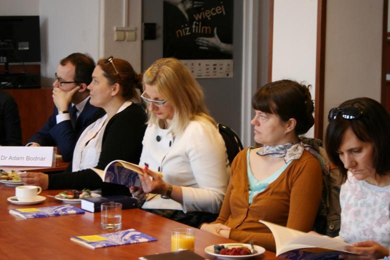 zdjęcie: kilka osób siedzi przy stole, niektórzy przeglądają raport w wersji papierowej