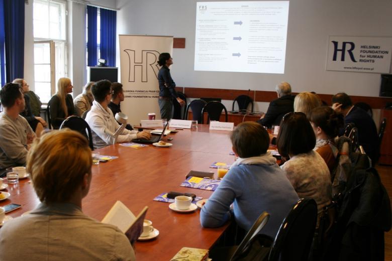 zdjęcie: kilkanaście osób siedzi przy stole, na ścianie wyświetlana jest prezentacja dotycząca wniosków z raportu