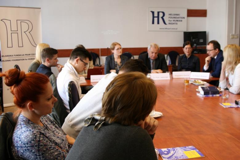 zdjęcie: kilkanascie osób siedzi przy stole, na stole leżą papierowe wersje raportu