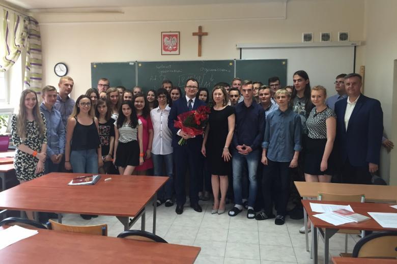 zdjęcie: duża grupa ludzi stoi w szkolnej sali lekcyjnej, w tle tablica szkolna