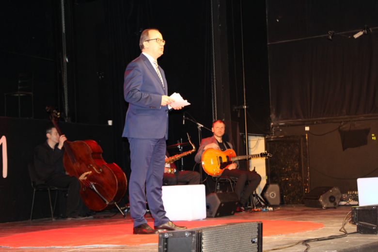 Mężczyzna stoi na scenie i przemawia