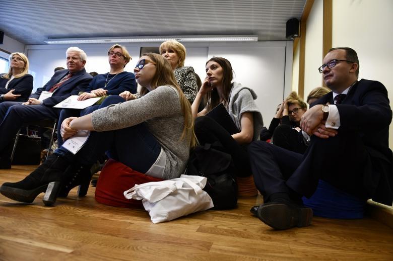 Ludzie siedzą na podłodze, wśród nich rzecznik praw obywatelskich