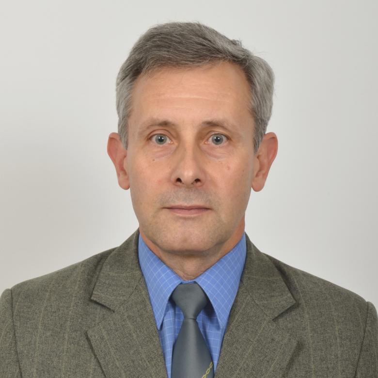 Mężczyzna w szaro-zielonym garniturze i niebieskiej koszuli