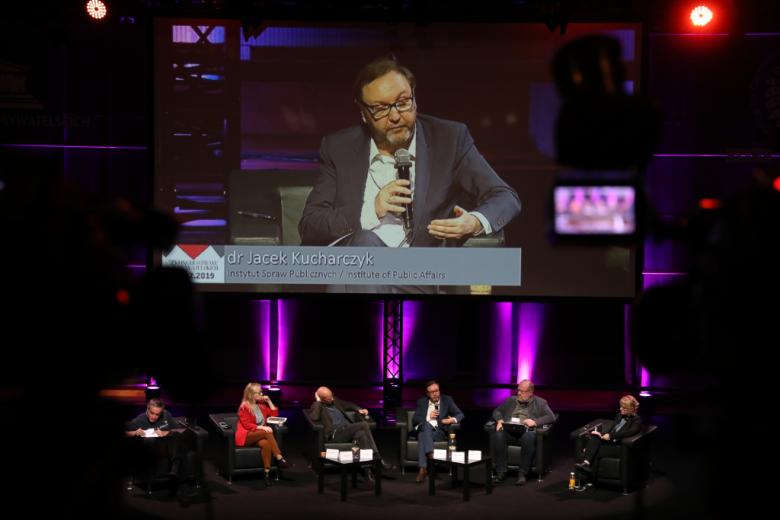 Paneliści na scenie, na ekranie za nimi powiększona postać z podpisem Jacek Kucharczykj