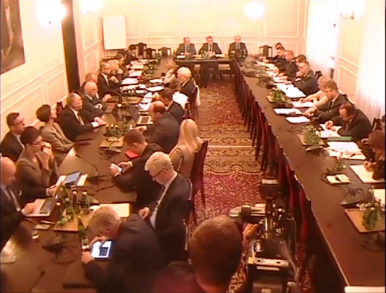 Screen komputerowy z transjmisji video. Posłowie siedzą w sali posiedzeń komisji