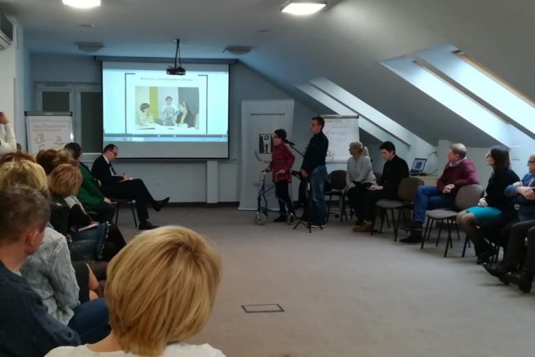 Dwoje ludzi robi prezentację zebranym na sali