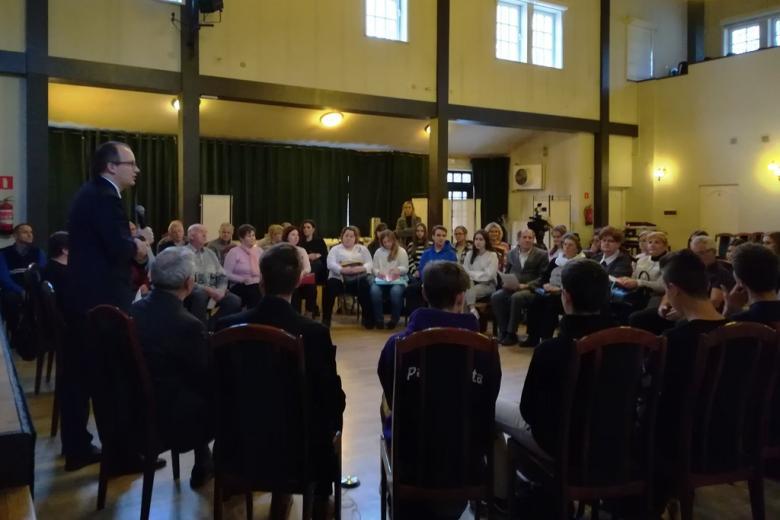 40 osób siedzi w kręgu, mężczyzna stoi, ujęcie z boku
