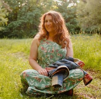 Młoda kobieta siedzi na trawie