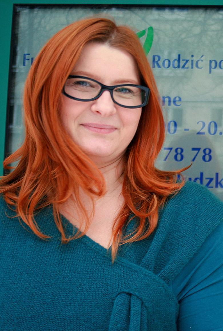 Kobieta w okularach z długimi rudymi włosami