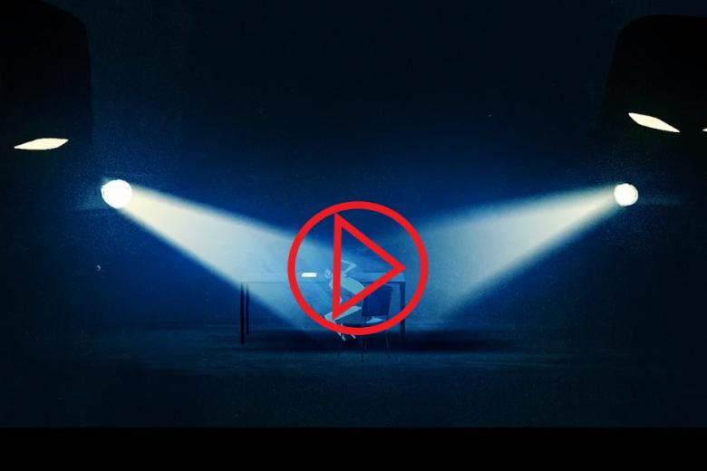 Człowiek oświetlony reflektorami, czerwony znak PLAY