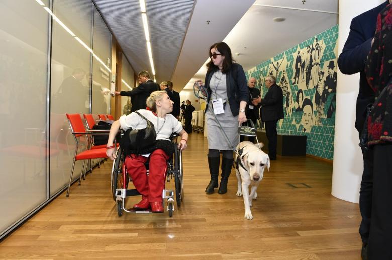 Kobieta z psem asystującym i kobieta na wózku idą korytarzem