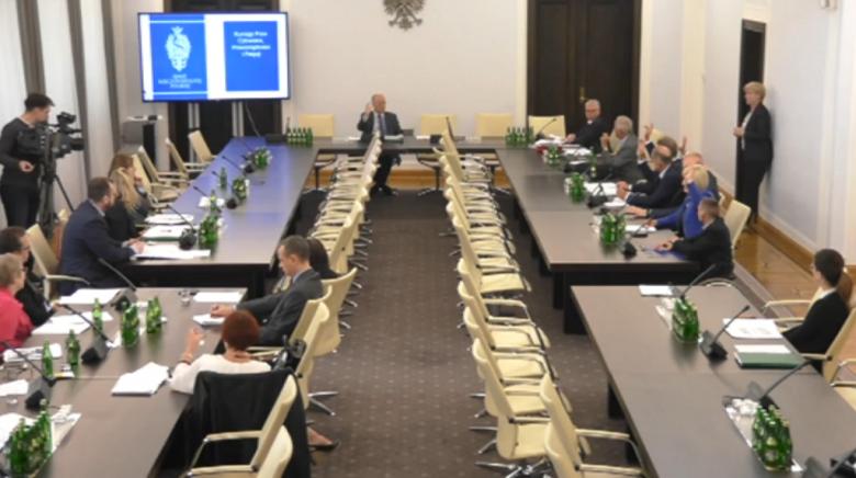 Zdjęcie z komputera: ludzie siedzą przy stole, niektórzy podnoszą rękę