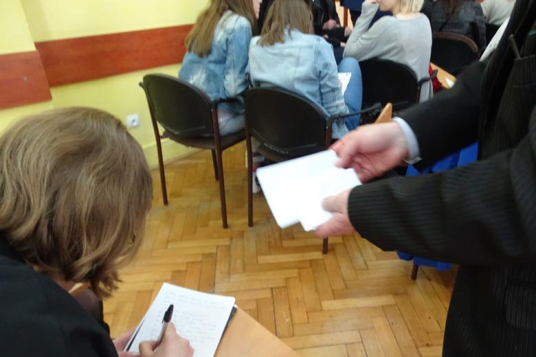 Mężczyzna (widać rękę) zbiera zapisane karteczki
