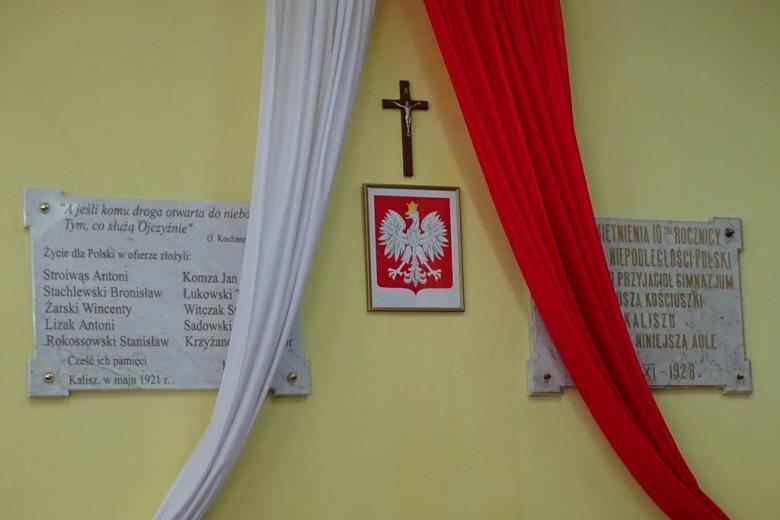 Dwie tablice na ścianie, biało-czerwona flaga i krzyż