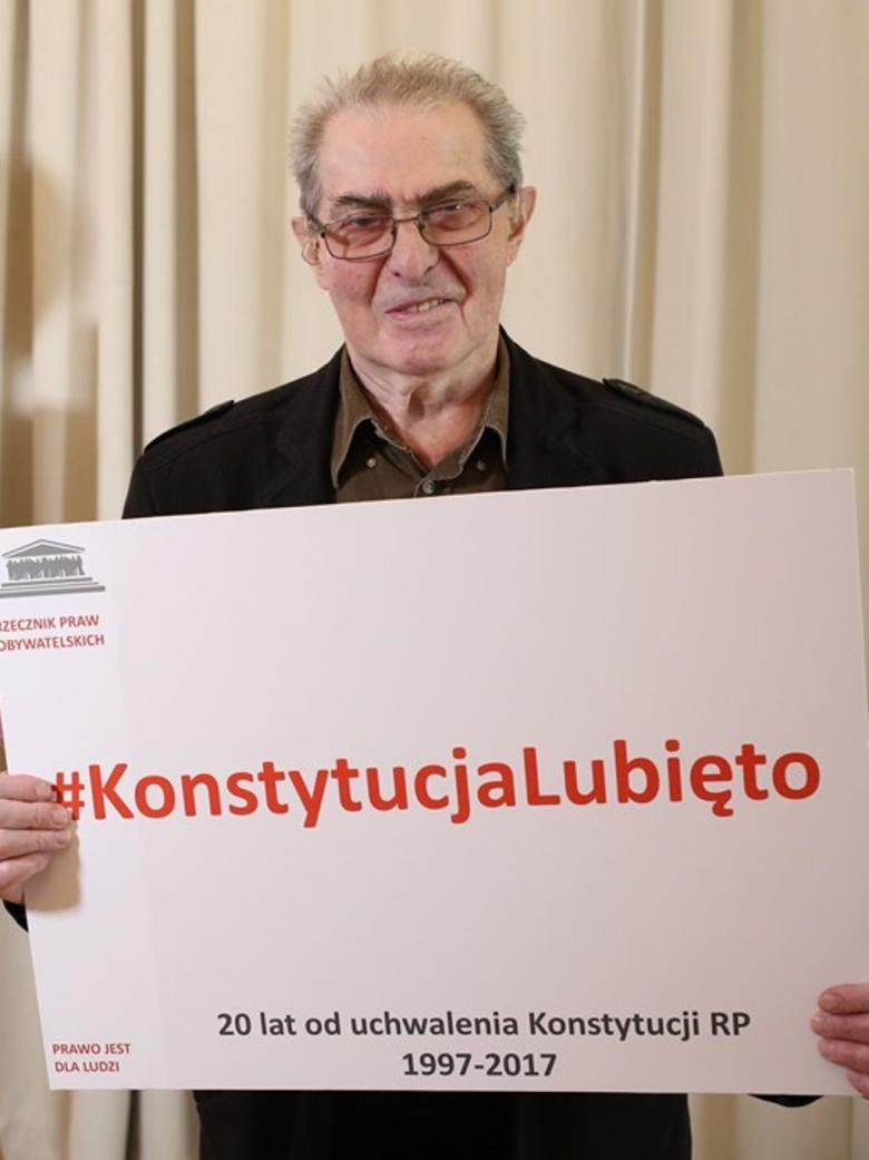 Mężczyzna trzyma tablice z napisem #KonstytucjaLubieTo