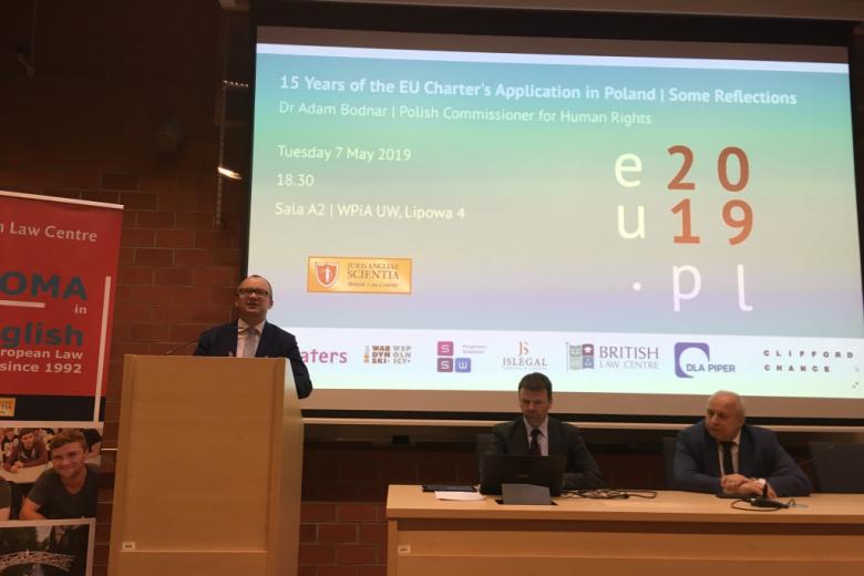 Mężczyzna na mównicy, dwaj inni w prezydium, na ścianie slajd z literami EU i PL i rokiem 2019