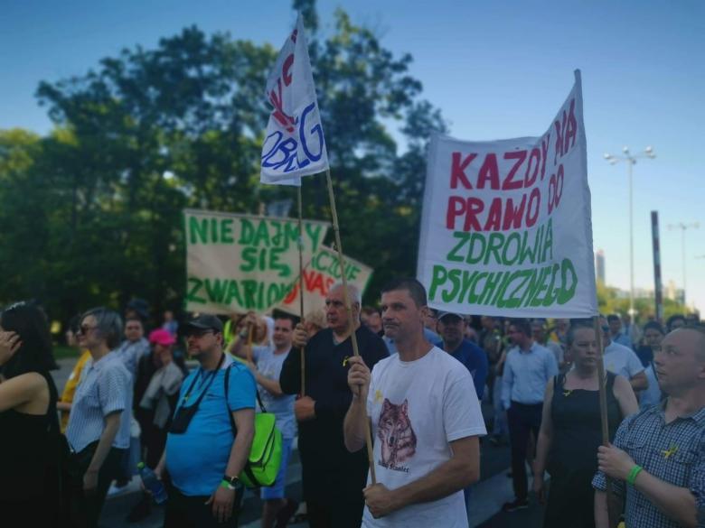 """Ludzie maszerują z transparentem """"Każdy ma prawo do zdrowia psychicznego"""""""