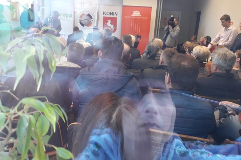 Tłum ludzi na sali, zdjęcie przez szybę w oknie