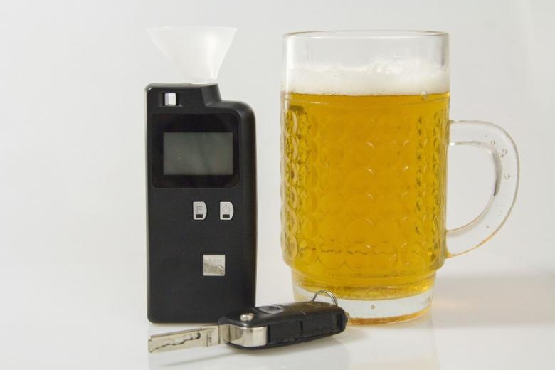 Kufel piwa, aparat do pomiaru alkoholu w organiźmie i kluczyki do samochodu